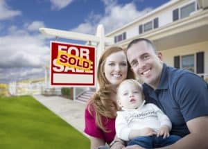 Happy couple holding baby in front of sold house