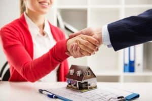 Two people shaking hands over a successful property agreement