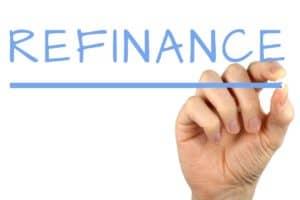 refinance written in light blue capital letters on reverse glass by a mans hand