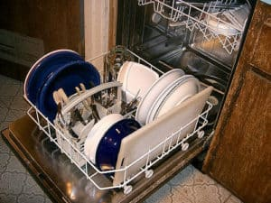 bottom tray of a dishwasher being loaded up with dishes and utensils