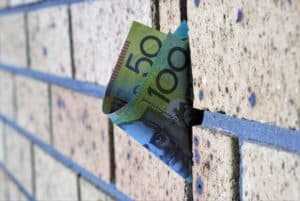 Australian one hundred dollar and fifty dollar note on wall. Selective focus. Concept of money's connection to building industry and infrastructure, home loans or mortgage.