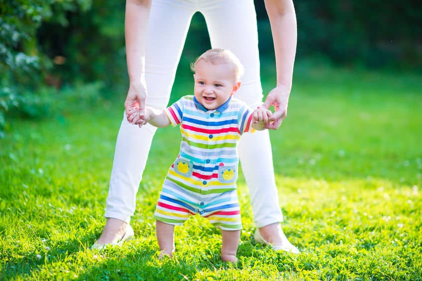 cute funny happy baby in a colorful shirt making his first steps on a green lawn in a sunny summer garden, mother holding his hands supporting by learning to walk