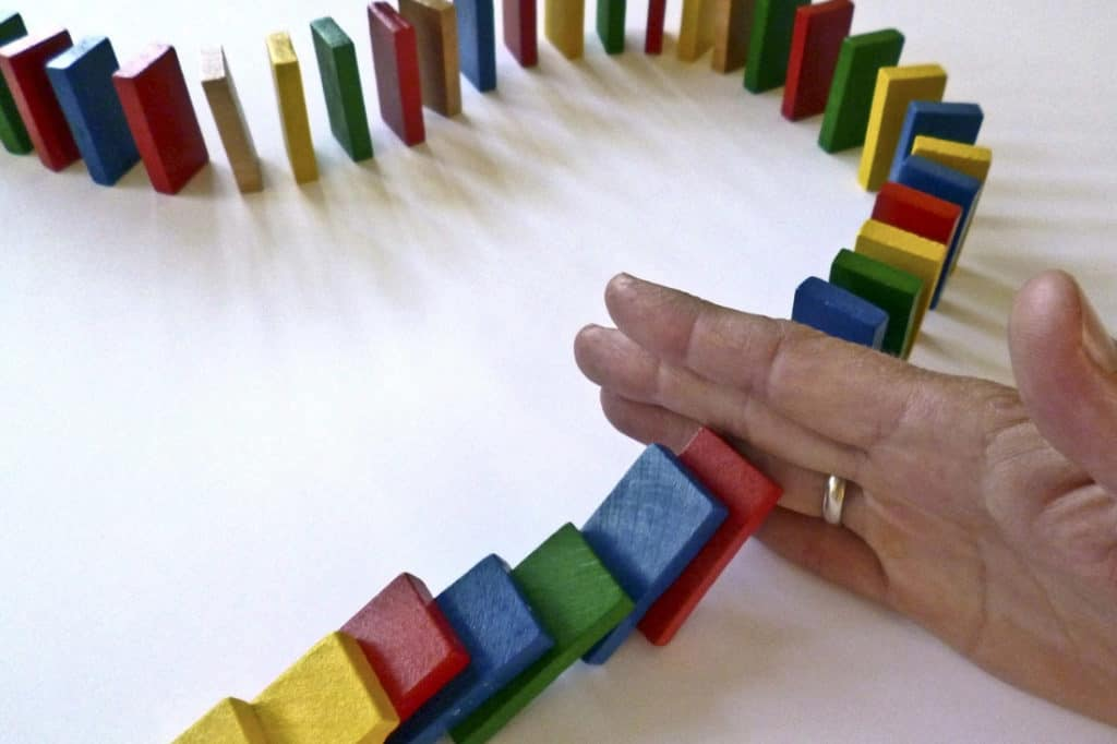 mortgage broker - a hand starting a long snaking line of dominoes to start falling over
