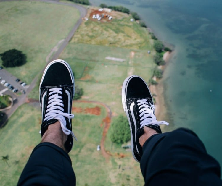 master broker sydney - looking down on a pair of feet in sand shoes parachuting down to earth